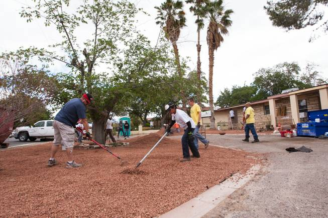 Volunteers work on the desert landscaping in the front yard of the home of photographer Robert Scott Hooper and wife Theresa Hooper as part of the Rebuilding Together Southern Nevada's annual neighborhood rebuilding event Saturday, April 26, 2014.