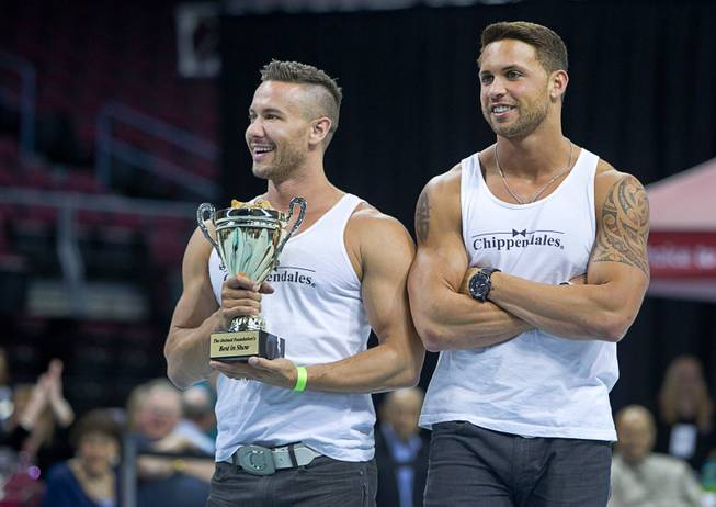 Special guests Ryan Stuart, left, and Matt marshall of the Chippendales hold the trophy during the Animal Foundation's 11th annual Best in Show competition at the Orleans Arena Sunday, April 27, 2014.
