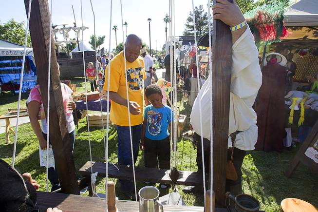 Lonnie Cureton and his son Donald, 5, learn about rigging during the second annual Pirate Festival Las Vegas in Lorenzi Park Sunday, April 27, 2014.