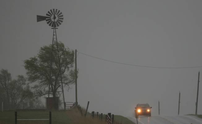 A vehicle tops a hill along U.S. Route 56 as a severe thunderstorm moves through the area near Baldwin City, Kan., Sunday, April 27, 2014. Severe storms are expected in the area most of the day.