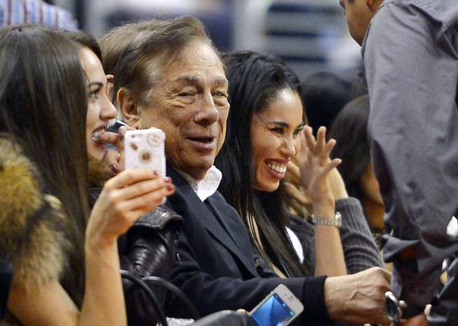 "In this photo taken Oct. 25, 2013, Los Angeles Clippers owner Donald Sterling, center, and V. Stiviano, right, watch the Clippers play the Sacramento Kings during the first half of an NBA basketball game in Los Angeles. The NBA is investigating a report of an audio recording in which a man purported to be Sterling makes racist remarks while speaking to Stiviano. NBA spokesman Mike Bass said in a statement April 26 that the league is in the process of authenticating the validity of the recording posted on TMZ's website. Bass called the comments ""disturbing and offensive."""