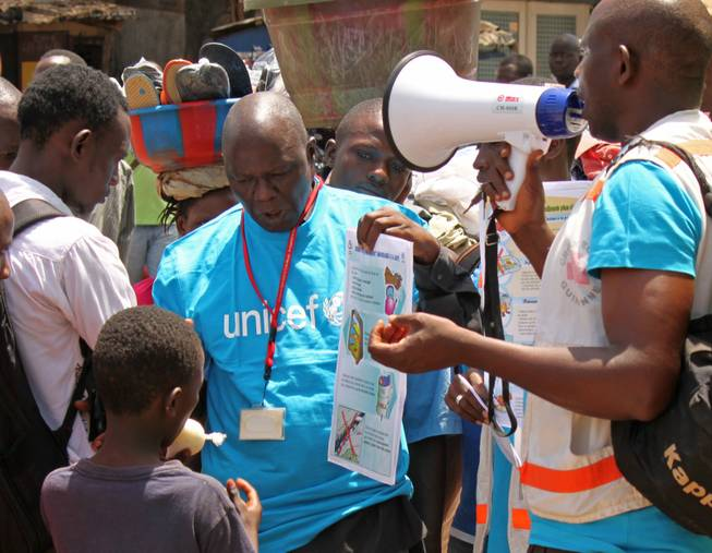 In this file photo taken on March 31, 2014, UNICEF health workers teach people about the Ebola virus and how to prevent infection, in Conakry, Guinea. The Ebola outbreak in West Africa has claimed some hundreds of lives, and is almost always fatal with horrific suffering including bursting blood vessels, there is no vaccine or known effective treatment, but it seems a handful of infected people have survived. However those who survive the horrors of the disease have to cope with being outcast by everybody, such is the fear people have of Ebola.