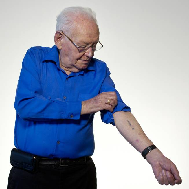 Israeli Holocaust survivor Asher Aud (Sieradski), 86, originally from Poland, shows his number tattooed on his arm by the Nazis at the Auschwitz concentration camp as he poses for a portrait in Jerusalem. Of all the atrocities he endured, Aud said the strongest memory is the one that was most traumatic — parting from his mother at the age of 14.