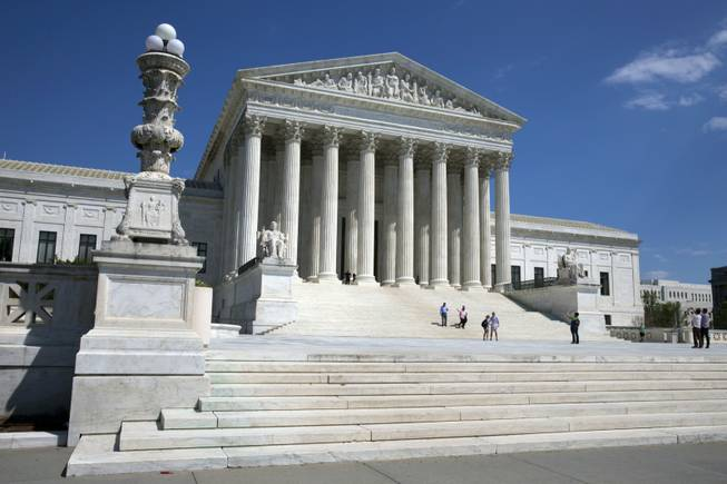 People walk on the steps of the U.S. Supreme Court in Washington. Two Supreme Court cases about police searches of cellphones without warrants present vastly different views of the ubiquitous device. Is it a critical tool for a criminal or is it an American's virtual home? How the justices answer that question could determine the outcome of the cases being argued Tuesday, April 29, 2014. A drug dealer and a gang member want the court to rule that the searches of their cellphones after their arrest violated their right to privacy in the digital age.