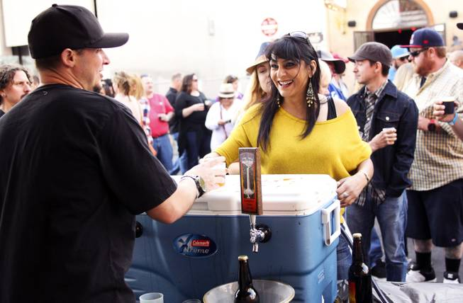 "Kevin Lingley at the Highwater Brewing booth hands festival goer Vandana Chima-Bhalla a sample of their beer during the ""Great Vegas Festival of Beer"" gathering on Fremont East Entertainment District Saturday, April 26, 2014."
