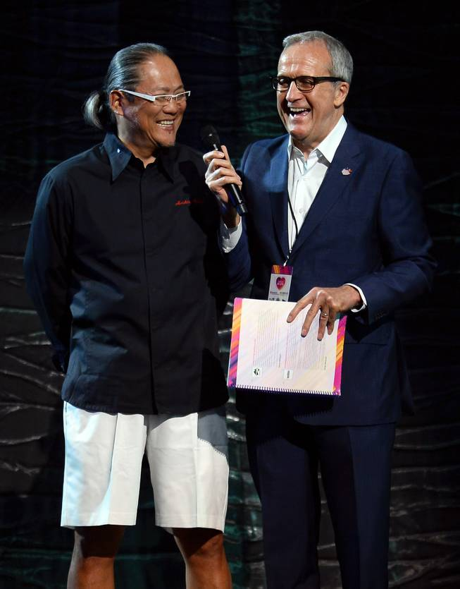 "Chef Masaharu Morimoto and Keep Memory Alive founder Larry Ruvo speak onstage during a live auction at the 18th annual Keep Memory Alive ""Power of Love Gala"" benefit for the Cleveland Clinic Lou Ruvo Center for Brain Health honoring Gloria Estefan and Emilio Estefan Jr. on Saturday, April 26, 2014, at MGM Grand Garden Arena."