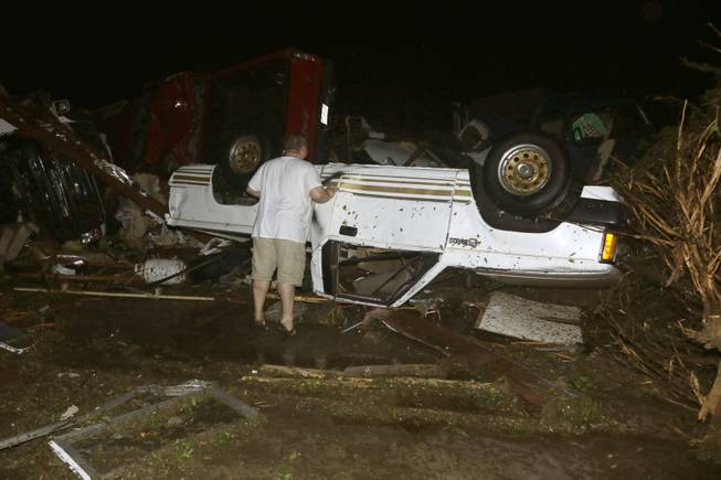 John Ward, an automobile and RV dealer, looks an tornado damage to one of his trucks in Mayflower, Ark., Sunday, April 27, 2014.