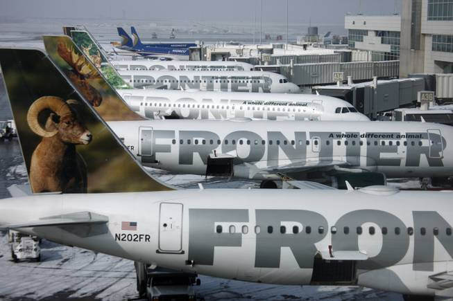 In this Feb. 22, 2010, file photo, Frontier Airlines jetliners sit stacked up at gates along the A concourse at Denver International Airport.