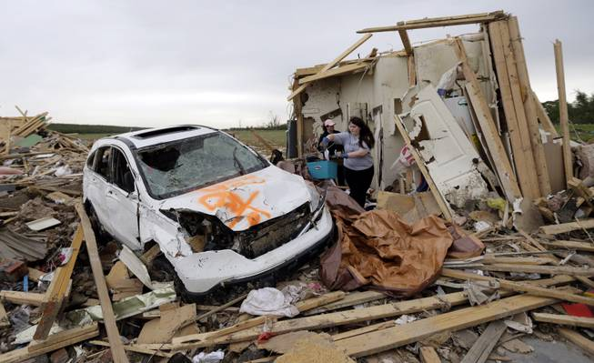 Haley Hracke, front, and Melissa Nichols, search for belongings at a friend's home that was destroyed by Sunday's tornado, Tuesday, April 29, 2014, in Vilonia, Ark. A dangerous storm system that spawned a chain of deadly tornadoes over three days flattened homes and businesses, forced frightened residents in more than half a dozen states to take cover and left tens of thousands in the dark Tuesday morning.