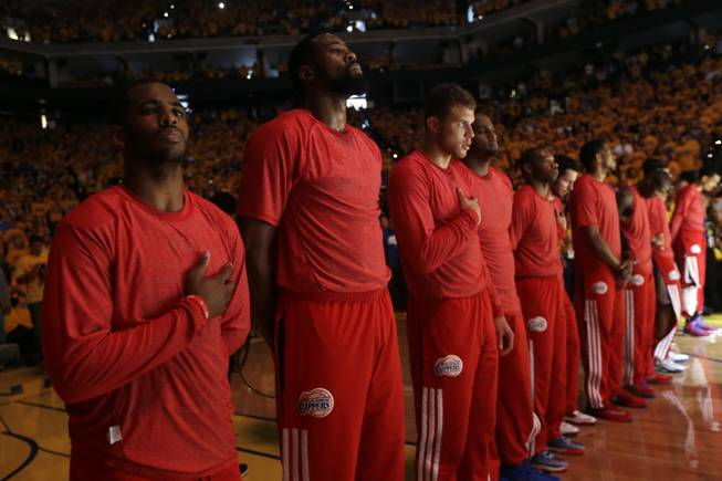 Los Angeles Clippers players listen to the national anthem wearing their warmup jerseys inside out to protest alleged racial remarks by team owner Donald Sterling before Game 4 of an opening-round NBA basketball playoff series against the Golden State Warriors on Sunday, April 27, 2014, in Oakland, Calif.