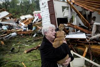 Constance Lambert embraces her dog after finding it alive when returning to her destroyed home in Tupelo, Miss., Monday, April 28, 2014. Lambert was at an event away from her home when the tornado struck and rushed back to check on her pets.