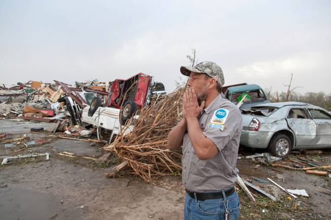 John Smith reacts after seeing what's left of his auto repair shop in Mayflower, Ark., Monday, April 28, 2014, after a tornado struck the town late Sunday. Mayflower was hit hard Sunday after a tornado system ripped through several states in the central U.S. and left more than a dozen dead in a violent start to this year's storm season, officials said.