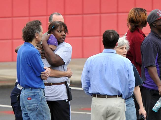 FedEx employee Lisa Aiken, is embraced by a co-worker as other FedEx employees gather following a shooting at the FedEx facility in Kennesaw, Ga., on Tuesday, April 29, 2014.