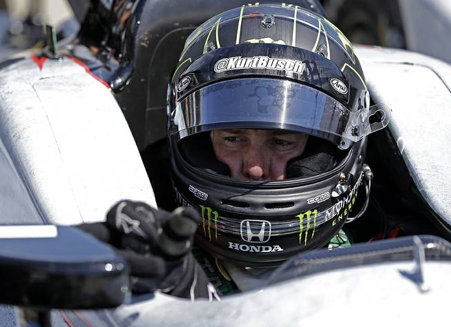 Race driver Kurt Busch adjusts the mirror of his car during a break in practice at Indianapolis Motor Speedway during the Rookie Orientation Program in Indianapolis, Tuesday, April 29, 2014.