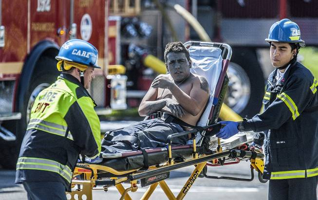 An injured worker is moved toward a waiting ambulance after an explosion was reported at a business in La Habra, Calif., Tuesday, April 29, 2014.