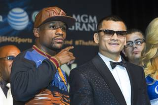 WBC welterweight champion Floyd Mayweather Jr., left, and WBA champion Marcos Maidana of Argentina pose during a news conference at the MGM Grand Wednesday, April 30, 2014. The two champions will meet in a WBC/WBA unification fight at the MGM Grand Garden Arena on Saturday.