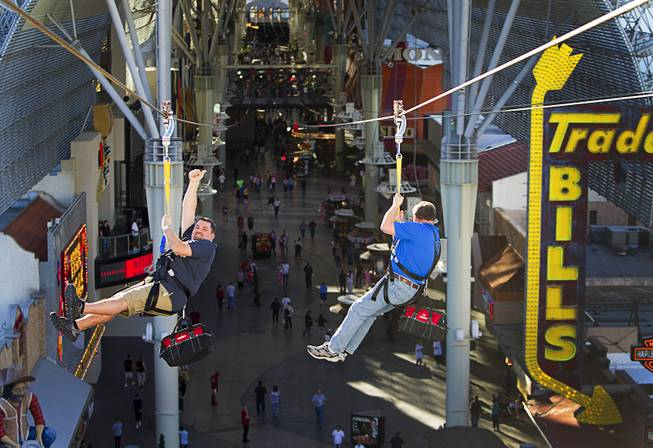 "Russ Dostal (L) gives a thumbs up as he tries the new 850-feet-long SlotZilla Zipline with Tom Delaney at the Fremont Street Experience in downtown Las Vegas, Wednesday, April 30, 2014. A higher and longer 1700-feet-long Zoomline, which will propel flyers in a horizontal ""superman"" position at speeds up to 35 mph, is expected to open in June. The zip-line, part of the $12 million SlotZilla project, opened Sunday."