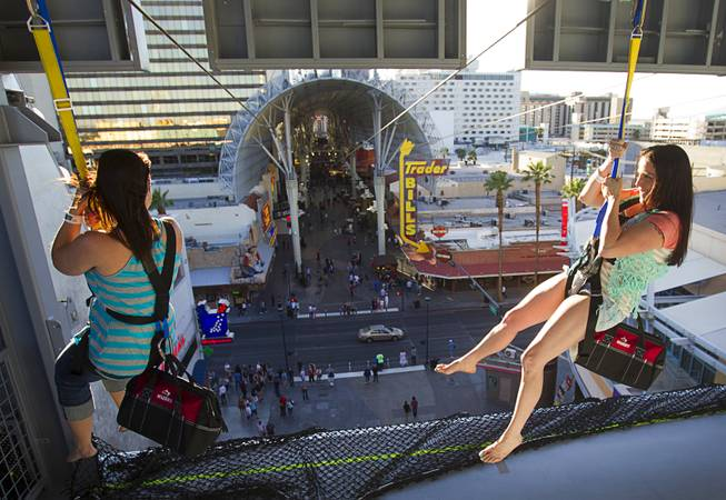 "Tourists hang from a 77-foot-high launching area at the new 850-feet-long SlotZilla Zipline at the Fremont Street Experience in downtown Las Vegas, Wednesday, April 30, 2014. A higher and longer 1700-feet-long Zoomline, which will propel flyers in a horizontal ""superman"" position at speeds up to 35 mph, is expected to open in June. The zip-line, part of the $12 SlotZilla million project, opened Sunday."
