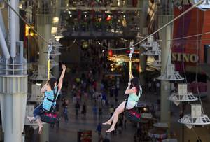 "A pair of tourists from Tennesee try out the new 850-feet-long SlotZilla Zipline at the Fremont Street Experience in downtown Las Vegas, Wednesday, April 30, 2014. A higher and longer 1700-feet-long Zoomline, which will propel flyers in a horizontal ""superman"" position at speeds up to 35 mph, is expected to open in June. The zip-line, part of the $12 million SlotZilla project, opened April 27, 2014."