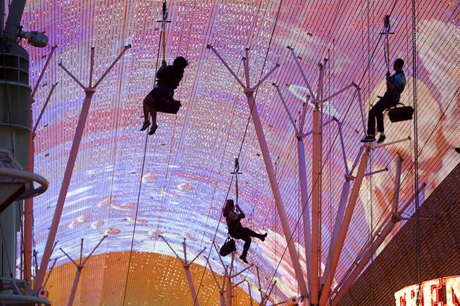 "People pass under the Viva Vision canopy as they try out the  new 850-feet-long SlotZilla Zipline at the Fremont Street Experience in downtown Las Vegas, Wednesday, April 30, 2014. A higher and longer 1700-feet-long Zoomline, which will propel flyers in a horizontal ""superman"" position at speeds up to 35 mph, is expected to open in June. The zip-line, part of the $12 million SlotZilla project, opened Sunday."