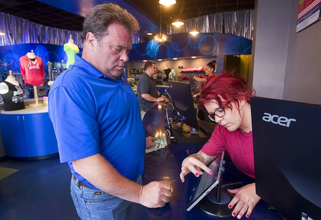 Ticket agent Kim Rush helps Tom Delaney of Saylorsburg, Penn. at the SlotZilla ticket office at the Fremont Street Experience in downtown Las Vegas, Wednesday, April 30, 2014. A 850-feet-long zip-line, part of the $12 million SlotZilla project, opened Sunday.