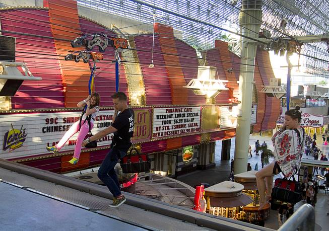 "Cirque du Soleil performers Jason Beitel, center, and Jenn Stafford, right, arrive at a landing ramp after riding the 850-feet-long SlotZilla Zipline at the Fremont Street Experience in downtown Las Vegas, Wednesday, April 30, 2014. A higher and longer 1700-feet-long Zoomline, which will propel flyers in a horizontal ""superman"" position at speeds up to 35 mph, is expected to open in June. The zip-line, part of the $12 million SlotZilla project, opened April 27, 2014."