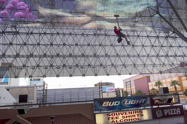 "A ""flyer"" passes under the Viva Vision canopy as he tries out the  new 850-feet-long SlotZilla Zipline at the Fremont Street Experience in downtown Las Vegas, Wednesday, April 30, 2014. A higher and longer 1700-feet-long Zoomline, which will propel flyers in a horizontal ""superman"" position at speeds up to 35 mph, is expected to open in June. The zip-line, part of the $12 million SlotZilla project, opened Sunday."