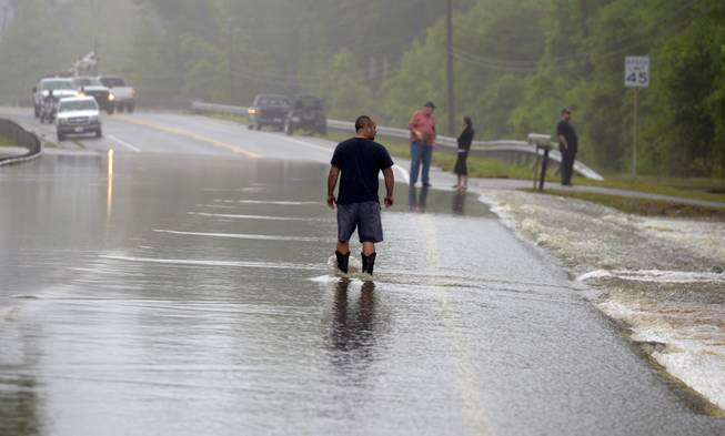 A man walks along a flooded stretch of Mobile Highway in Beulah, Fla., following heavy rains near Pensacola, Fla., Wednesday, April 30, 2014.