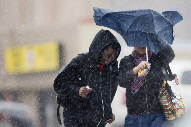Pedestrians walk with little protection from their collapsed umbrella during a rainstorm, Wednesday, April 30, 2014, in Philadelphia. The area can expect widespread showers with possible thunderstorms with a flood watch in effect through Thursday morning.