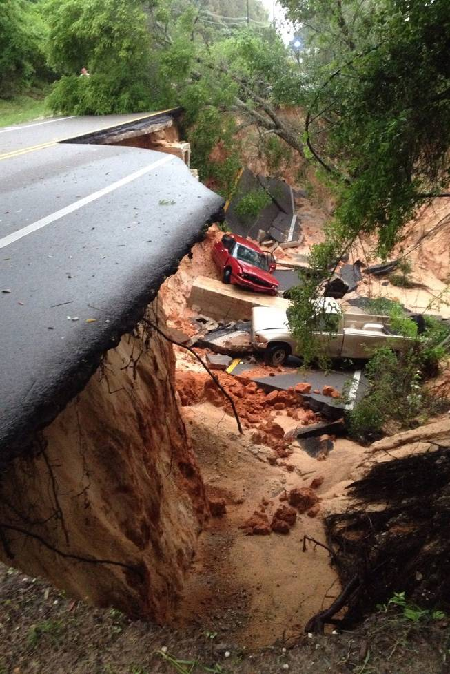 A car lies at the bottom of a ravine after the Scenic Highway collapsed near Pensacola, Fla., Wednesday April 30, 2014. Heavy rains and flooding have left people stranded in houses and cars in the Florida Panhandle and along the Alabama coast. According to the National Weather Service, an estimated 15-20 inches of rain has fallen in Pensacola in the past 24 hours.