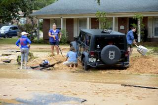 Barbara Erdos, far left, watches as Marguerite Lysek, left, Dr. Zoltan Erdos, kneeling, and Kristen Broussard, right help dig Erdos' stuck Jeep out of axel-deep mud on Piedmont Street after flood-water devastation caused by torrential rains in Pensacola, Fla., Wednesday, April 30, 2014.