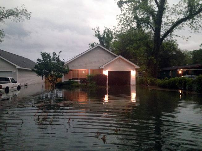 In this photo provided by Kyle Smith, floodwaters surround Smith's home in Pensacola, Fla., on Wednesday, April 30, 2014. Smith had to evacuate his home with his 18-month-old son Tuesday night after severe weather hit the Florida Panhandle, causing widespread flooding.
