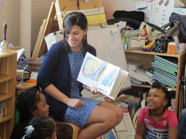 "In this April 10, 2014, file photo, student teacher Franchesca Moreno, 21, reads to Andreanna Thomas, 6, right, and Alana Cawthon, upper left, at Bennett Park Montessori School in Buffalo, N.Y. Moreno is among the first future New York teachers required to pass a kind of ""bar exam"" to become professionally certified."