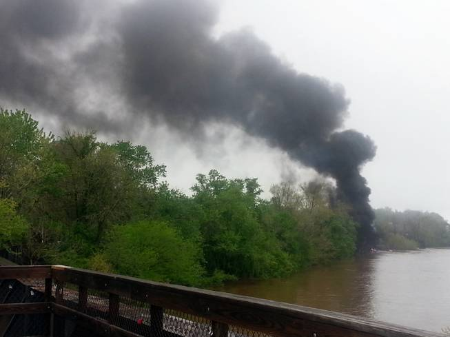 This mobile phone photo provided Ali Hallock shows smoke rising after several CSX tanker cars carrying crude oil derailed, from the view of a bridge over the James river, Wednesday, April 30, 2014, in Lynchburg, Va. Authorities evacuated numerous buildings Wednesday after the derailment.