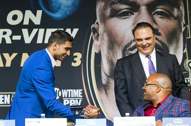 Welterweight boxer Amir Khan, left, of Britain greets Leonard Ellerbe, CEO of Mayweather Promotions, as Richard Schaefer, CEO of Golden Boy Promotions, looks on during a news conference for undercard boxers at the MGM Grand Thursday, May 1, 2014.