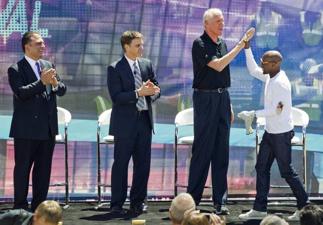 Undefeated boxing champion Floyd Mayweather Jr. greets former NBA star Bill Walton and others onstage at the AEG and MGM Resorts International groundbreaking VIP/media event atop a bulldozer on Thursday, May 1, 2014, in Las Vegas.
