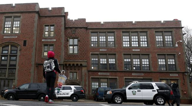 A girl crosses the street near police vehicles outside of Teaneck High School, where more than 60 students were arrested during an overnight break-in, Thursday, May 1, 2014, in Teaneck, N.J.