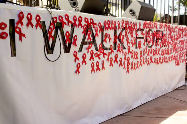 "The ""I Walk For"" stage banner filled with red ribbons is seen during the 2013 Aids Walk held at UNLV, Sunday, April 13, 2013. Participants were asked to write the name of the person they're walking for on the red paper ribbons and place them on the banner."