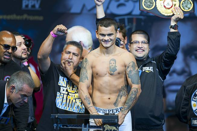 WBA welterweight champion Marcos Maidana of Argentina poses on the scale during an official weigh-in at the MGM Grand Garden Arena Friday, May 2, 2014. Maidana faces WBC welterweight champion Floyd Mayweather Jr.  in a WBC/WBA unification fight at the arena on Saturday.