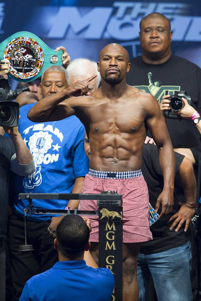 WBC welterweight champion Floyd Mayweather Jr.  poses on the scale during an official weigh-in at the MGM Grand Garden Arena Friday, May 2, 2014. Mayweather faces WBA welterweight champion Marcos Maidana of Argentina in a WBC/WBA unification fight at the arena on Saturday.
