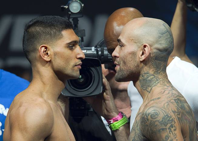 Amir Khan, left, of Britain and Luis Collazo face off during an official weigh-in at the MGM Grand Garden Arena Friday, May 2, 2014. The boxers will meet for a welterweight fight at the arena on Saturday.