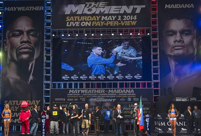 Amir Khan of Britain is shown on a video screen as he makes his way to the stage during an official weigh-in at the MGM Grand Garden Arena Friday, May 2, 2014. Khan will face Luis Collazo  for a welterweight fight at the arena on Saturday.