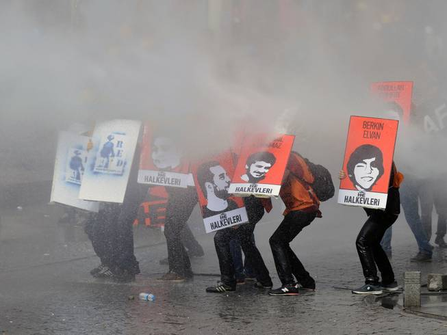 Protesters hold posters with images of the victims of the last year's protests as riot police use water cannons and teargas to disperse thousands of people trying to reach the city's main Taksim Square to celebrate May Day in Istanbul, Turkey, Thursday, May 1, 2014. Clashes erupted between May Day demonstrators and riot police as crowds determined to defy a government ban tried to march to the city's iconic Taksim Square. Security forces pushed back demonstrators with water cannons and tear gas.