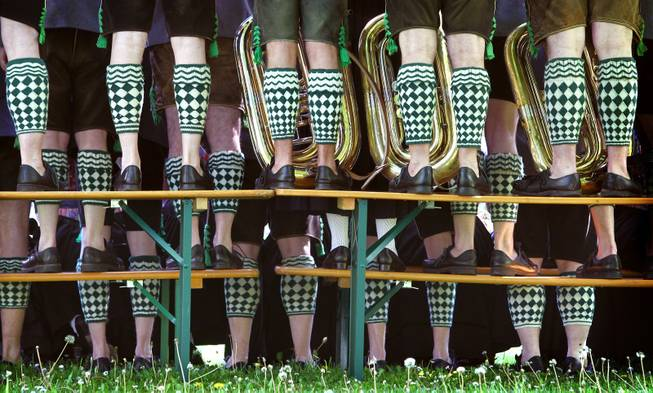 Musicians of the band Garmisch wearing traditional Bavarian costumes stand on beer benches and tables to take a group photo during May Day celebrations in the spa park of Garmisch-Partenkirchen, southern Germany, Thursday, May 1, 2014.