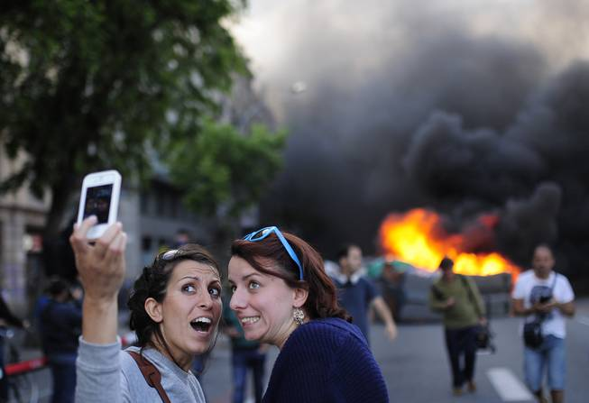 Tourists take a 'selfie' picture as demonstrators burn a trash container during a May Day rally in Barcelona, Spain, Thursday, May 1, 2014. Tens of thousands of workers marked May Day in European cities with a mix of anger and gloom over austerity measures imposed by leaders trying to contain the eurozone's intractable debt crisis.