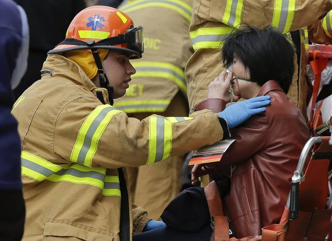 A New York City fire department EMT assists a woman who was evacuated from a subway train after it derailed in the Queens borough of New York, Friday, May 2, 2014.