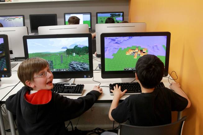 "Bobby Craig, left, and Doogy Lee create worlds in ""Minecraft"" that parallel what they have been reading in ""The Hobbit"" as part of their fifth grade class studies at Quest Academy in Palatine, Ill."