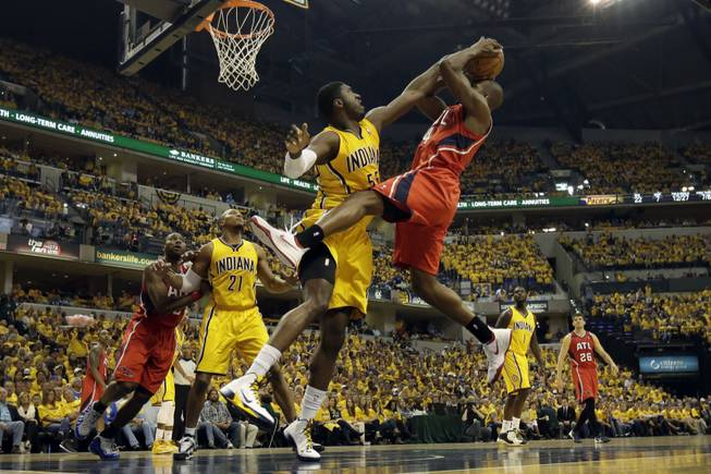 Indiana Pacers center Roy Hibbert, front left, tries to block the shot of Atlanta Hawks forward Paul Millsap during the first half in Game 7 of a first-round NBA basketball playoff series in Indianapolis, Saturday, May 3, 2014.