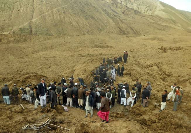 Afghans search for survivors after Friday's landslide buried Abi-Barik village in Badakhshan province, northeastern Afghanistan, Saturday, May 3, 2014. Afghan rescuers and hundreds of volunteers armed with shovels rushed on Saturday to help villagers hit by a massive landslide in the remote northeast a day earlier, officials said, while fears of a new torrent of mud and earth complicated rescue efforts.