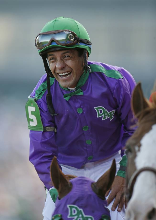 Victor Espinoza smiles after riding California Chrome to a victory during the 140th running of the Kentucky Derby horse race at Churchill Downs on Saturday, May 3, 2014, in Louisville, Ky.